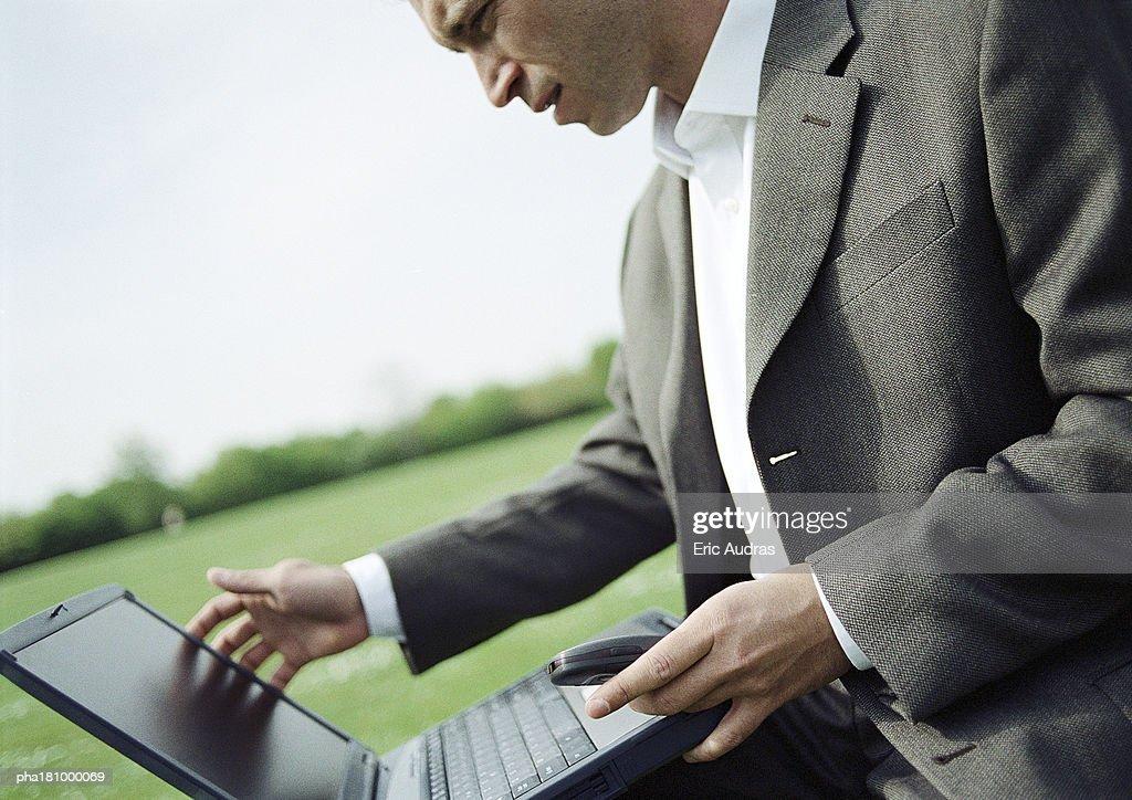 Businessman using laptop computer outdoors, close-up : Stockfoto