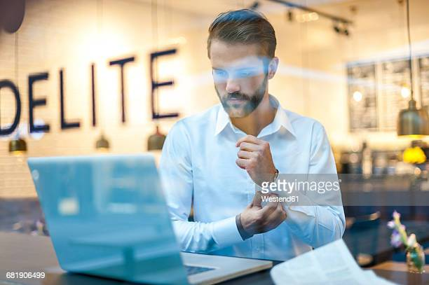 businessman using laptop in a cafe - western script stock pictures, royalty-free photos & images