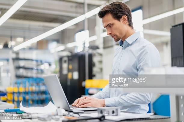 businessman using laptop in a factory - ingenieur stock-fotos und bilder