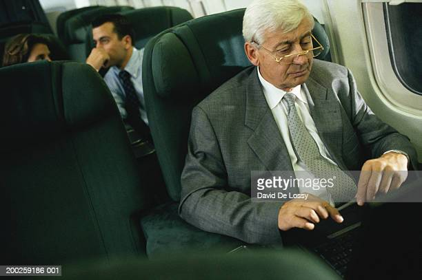 Businessman using laptop in airplane