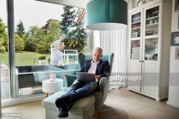 businessman using laptop in armchair at home with son behind windowpane in garden - abgelenkt stock-fotos und bilder