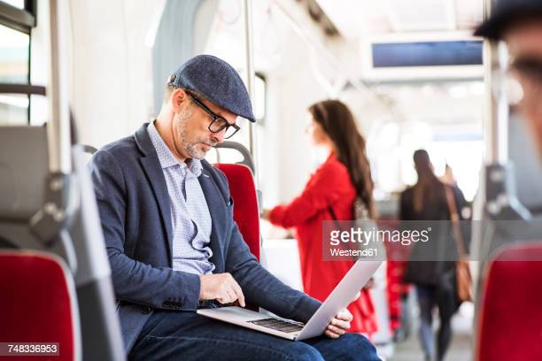 Businessman using laptop in bus