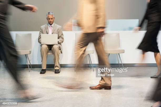 Businessman using laptop in busy lobby area