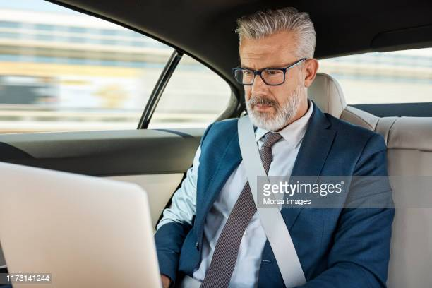 businessman using laptop in car - 車内 ストックフォトと画像