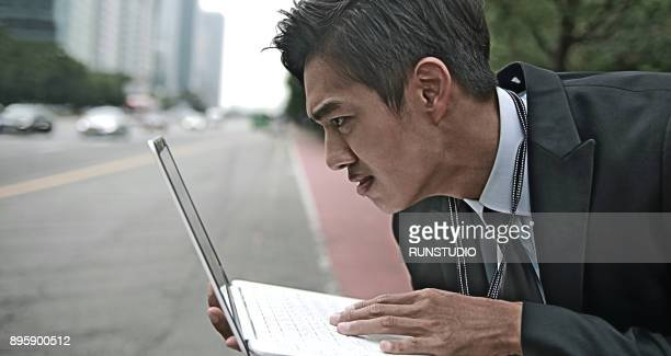 Businessman using laptop in city