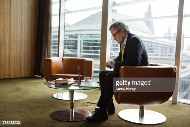 Businessman using laptop in coffee area in office, London, UK
