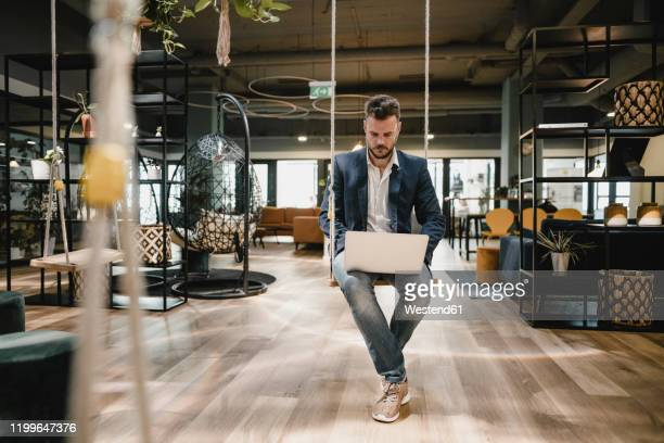 businessman using laptop in coworking space, sitting on swing - open plan stock pictures, royalty-free photos & images
