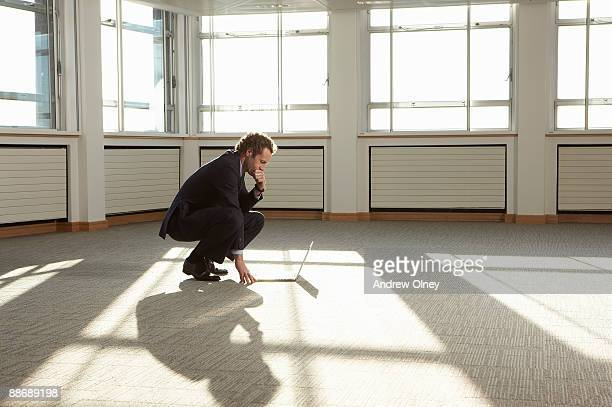 Businessman using laptop in empty office