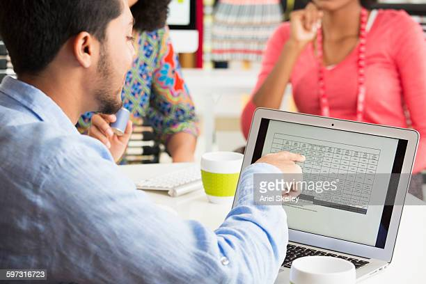 Businessman using laptop in office meeting