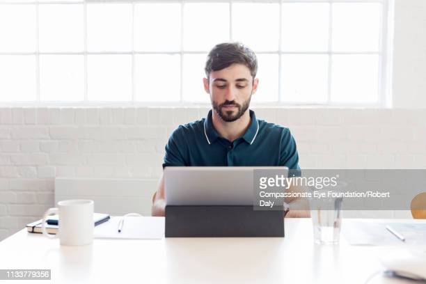 "businessman using laptop in office - ""compassionate eye"" stock pictures, royalty-free photos & images"