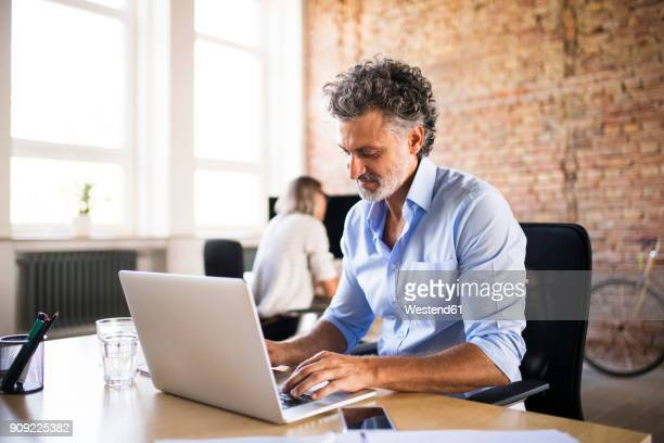 Businessman using laptop in office with colleague in background