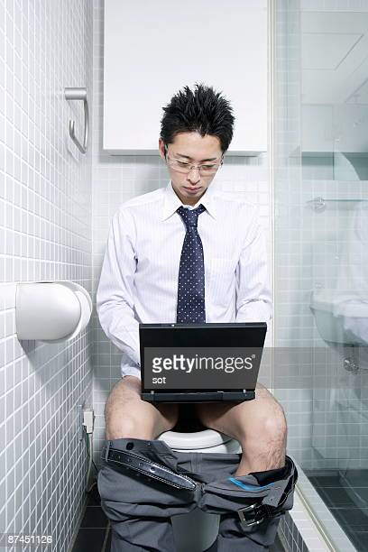 Businessman using laptop in restroom