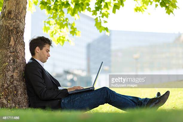 Businessman using laptop in the park on a sunny day