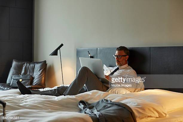 Businessman using laptop on bed in hotel room
