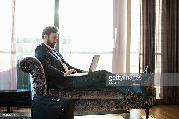 Businessman using laptop on chaise longue in hotel room