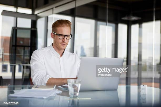 businessman using laptop on desk in office - shirt stock pictures, royalty-free photos & images