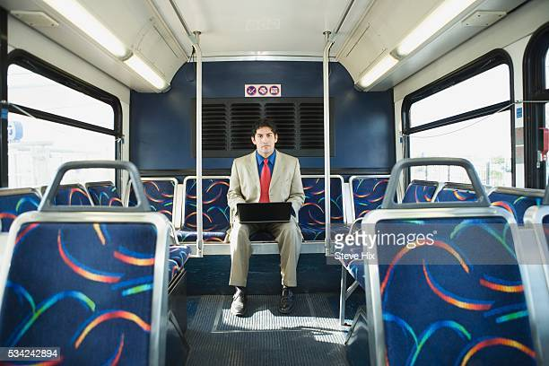Businessman Using Laptop on Empty Bus