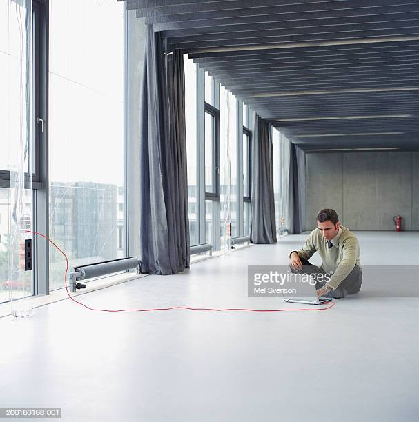 businessman using laptop on floor of empty office - one man only stock pictures, royalty-free photos & images