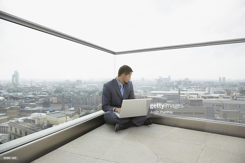 Businessman using laptop on rooftop : Stock-Foto