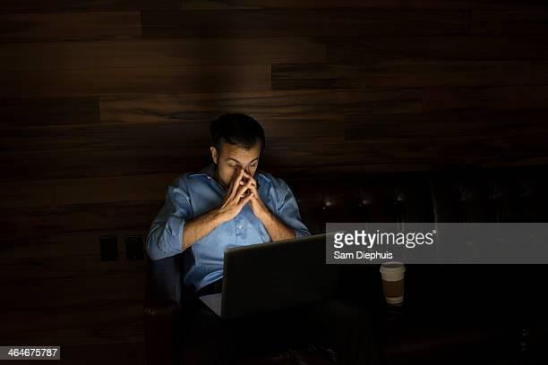 Businessman using laptop on sofa at night