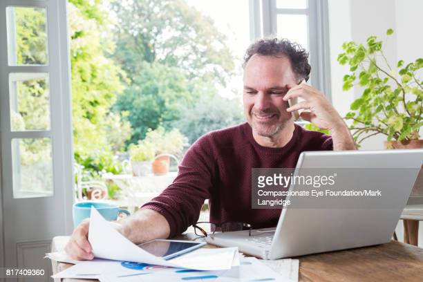 businessman using laptop paying bills online in kitchen - maroon stock pictures, royalty-free photos & images