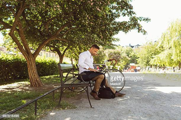 Businessman using laptop while sitting on bench at park