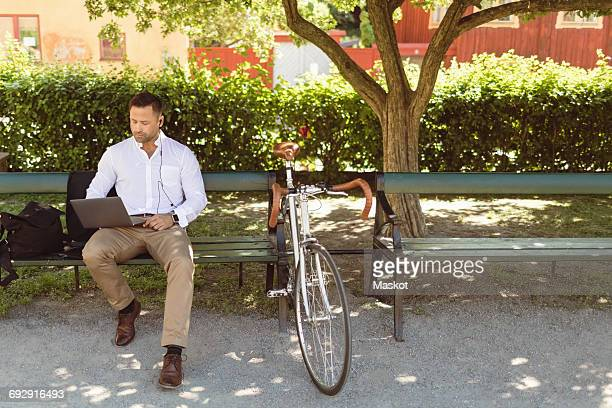Businessman using laptop while sitting on park bench