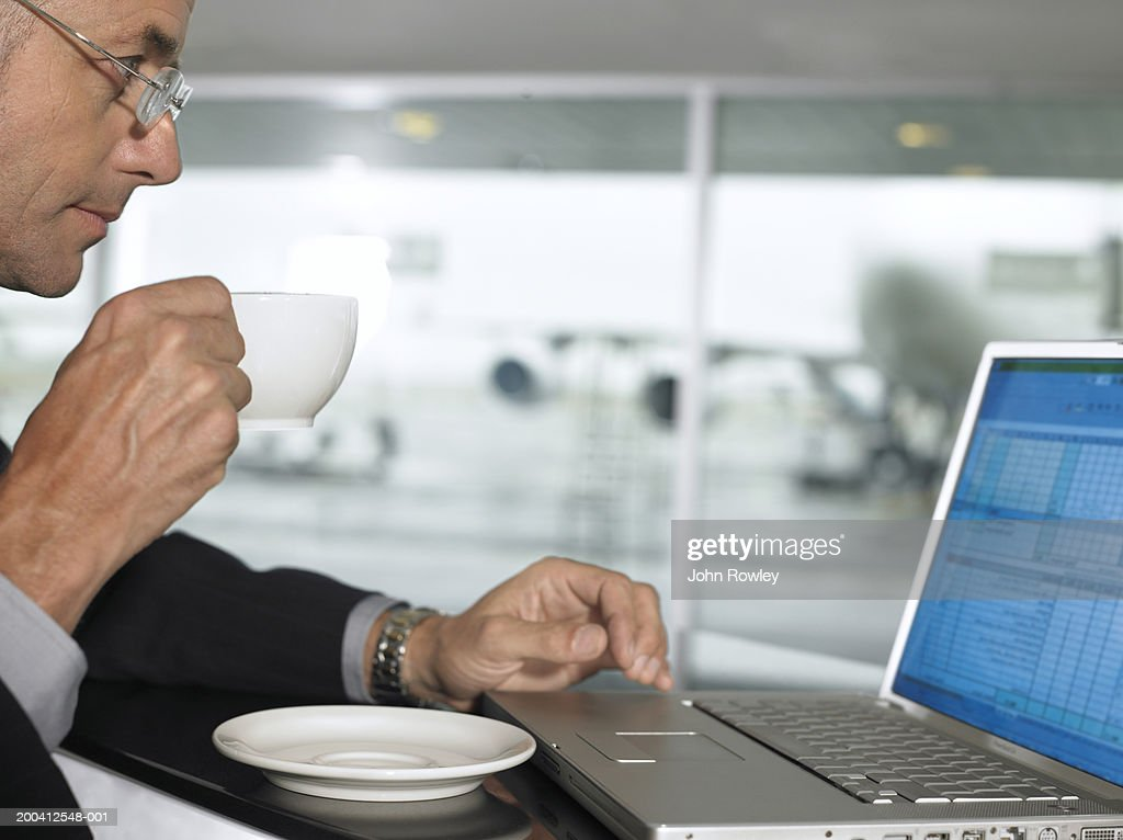 Businessman using laptop whilst drinking from cup, profile, close-up : Stock Photo