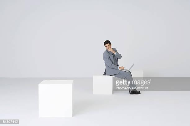 Businessman using laptop, whispering over shoulder