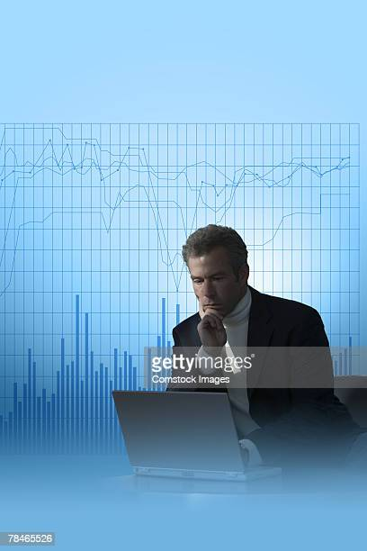 Businessman using laptop with graphs