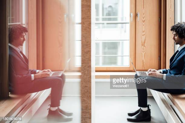 businessman using laptop with reflection of himself on glass at workplace - symmetry stock pictures, royalty-free photos & images