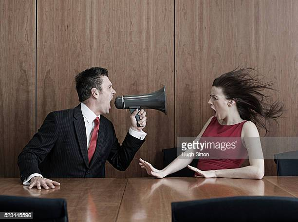 businessman using megaphone to shout at female colleague - hugh sitton stock pictures, royalty-free photos & images