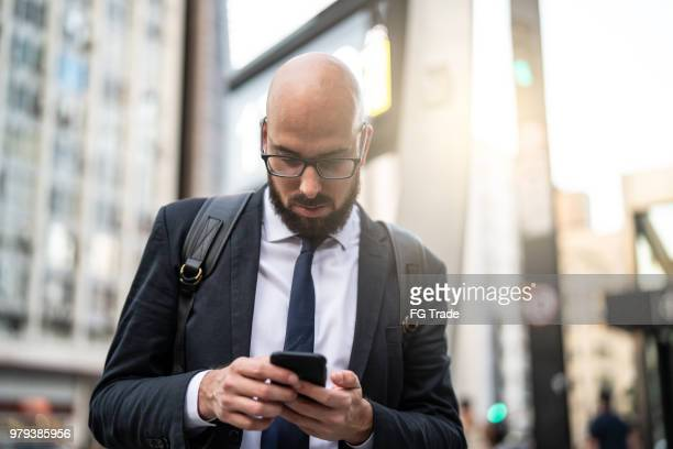 businessman using mobile at city - capital cities stock pictures, royalty-free photos & images