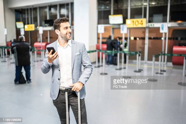 businessman using mobile on airport - heathrow stock pictures, royalty-free photos & images