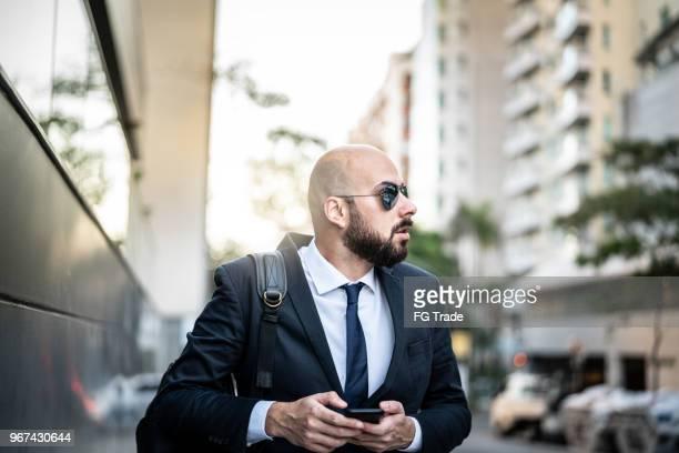 homem de negócios usando móvel na cidade - careca - fotografias e filmes do acervo
