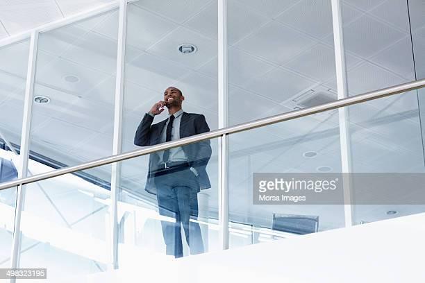 businessman using mobile phone against railing - la haye photos et images de collection
