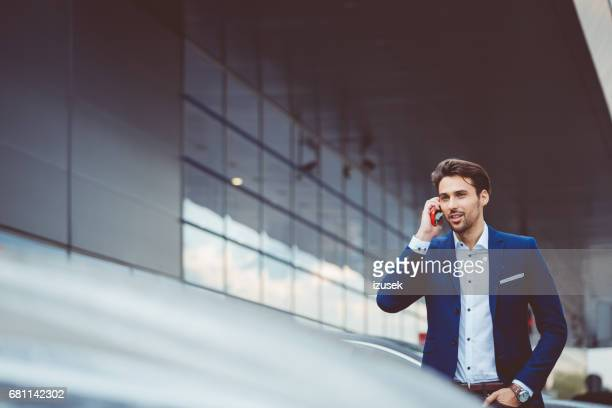 Businessman using mobile phone at airport parking lot