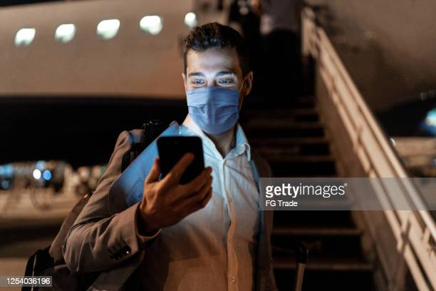 businessman using mobile phone at airport using protective mask - aeroplane stock pictures, royalty-free photos & images