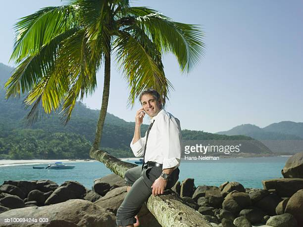 Businessman using mobile phone at beach, smiling