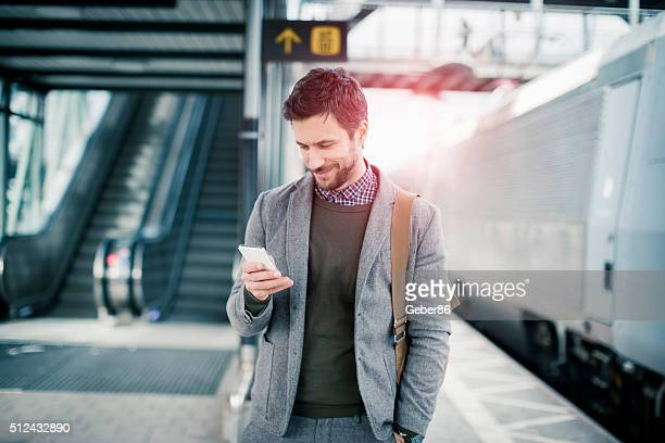 businessman using mobile phone at train station - onderweg stockfoto's en -beelden