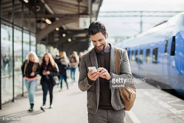 businessman using mobile phone at train station - draagbare informatie apparatuur stockfoto's en -beelden