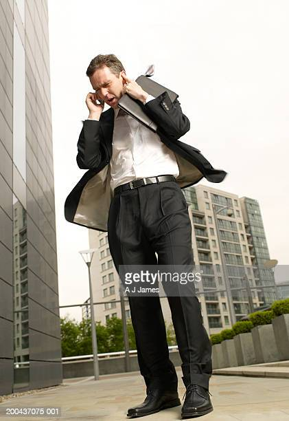 businessman using mobile phone, holding finger to ear, low angle view - fingers in ears stock pictures, royalty-free photos & images