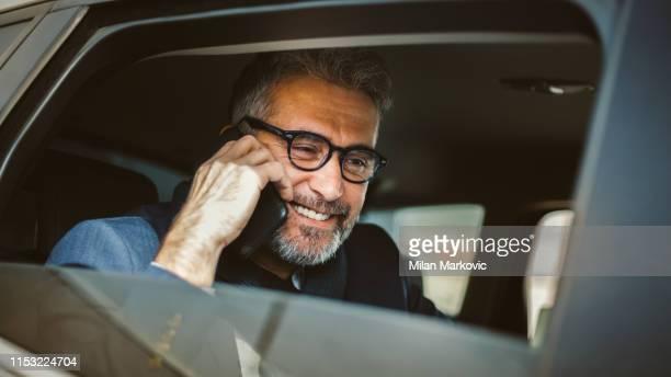 businessman using mobile phone in car - adulto di mezza età foto e immagini stock
