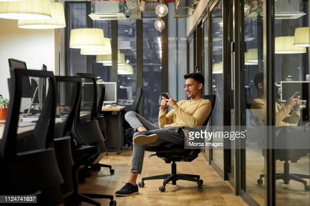 businessman using mobile phone in creative office - websurfen stock-fotos und bilder
