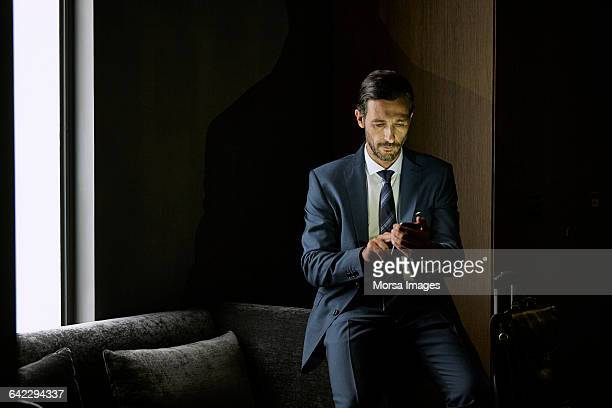 businessman using mobile phone in hotel room - westeuropa stock-fotos und bilder