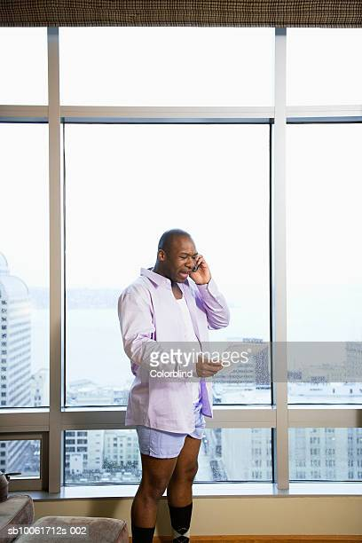 Businessman using mobile phone in hotel room, shouting