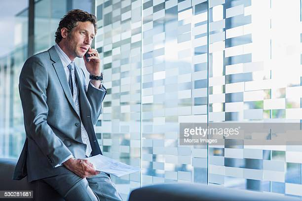 businessman using mobile phone in office - looking away stock pictures, royalty-free photos & images