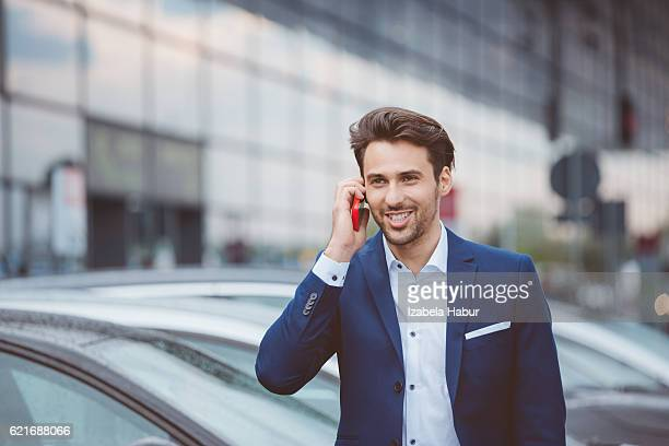 Businessman using mobile phone in parking lot