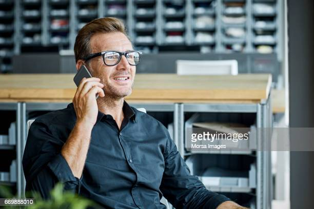 businessman using mobile phone in textile factory - usare il telefono foto e immagini stock