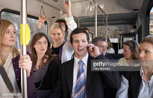 businessman using mobile phone, laughing on bus - irritation stock pictures, royalty-free photos & images